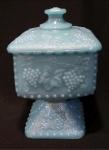 Antiga e rara bomboniere em vidro azul leitoso, parte superior quadrada e base no mesmo estilo. Possui relevos no corpo e tampa de uvas e folhas. Altura de 20 cm.